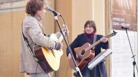 Rusland, Novosibirsk, April 2019: De straatmusici spelen gitaren en zingen liederen voor voorbijgangers Langzame Motie stock video
