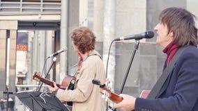 Rusland, Novosibirsk, April 2019: De straatmusici spelen gitaren en zingen liederen voor voorbijgangers Langzame Motie stock videobeelden