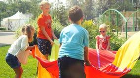 Rusland, Novosibirsk, 23 juli 2016 Gelukkige kinderen die met animators in heldere kostuums openlucht op het gras spelen bij Royalty-vrije Stock Foto