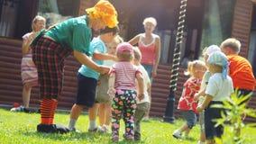 Rusland, Novosibirsk, 23 juli 2016 Gelukkige kinderen die met animators in heldere kostuums openlucht op het gras spelen bij Royalty-vrije Stock Fotografie