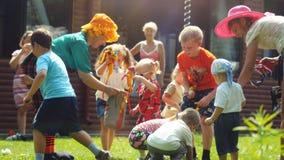 Rusland, Novosibirsk, 23 juli 2016 Gelukkige kinderen die met animators in heldere kostuums openlucht op het gras spelen bij Stock Fotografie