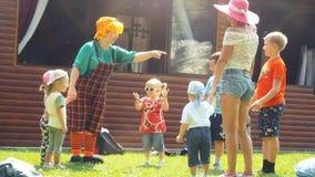 Rusland, Novosibirsk, 23 juli 2016 Gelukkige kinderen die met animators in heldere kostuums openlucht op het gras spelen bij Stock Afbeeldingen