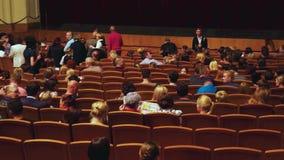 Rusland, Novosibirsk, 30 kan 2015 De mensen zitten op hun zetels vóór de prestaties in de bioscoop stock videobeelden
