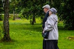 Rusland, Priozersk, Augustus 2016: Koppelen de bejaarden samen gaan onder het wapen op de houten gang Stock Fotografie