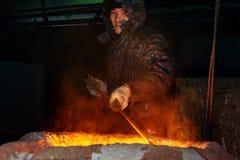 Rusland, Ryazan 14 Februari 2019 - de arbeider belemmert gesmolten metaal met een staaf in fabriek van metaal het gieten proces royalty-vrije stock afbeelding
