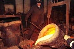Rusland, Ryazan 14 Februari 2019 - de arbeider belemmert gesmolten metaal met een staaf in fabriek van metaal het gieten proces royalty-vrije stock fotografie
