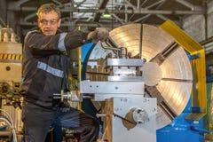2019 01 16: Rusland, Ryazan Mens die grote industriële CNC draaibankmachine aanpassen die de staalstaaf snijden stock fotografie