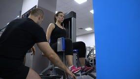 Rusland, Samara - November 13, 2018: Vrouw die hurkende oefening doen bij de gymnastiek met een persoonlijke trainer stock videobeelden