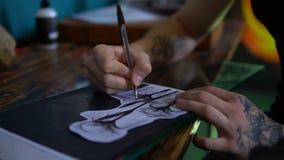 RUSLAND, SAMARA - 21 SEPTEMBER, 2018: de kunstenaar trekt een schets van de tatoegering op papier op de Desktop, hoogste mening stock footage