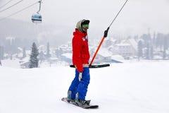 Rusland, Sheregesh 2018 11 18 Snowboarder in professionele uitrusting beklimmen omhoog op skilift bergen E royalty-vrije stock foto's