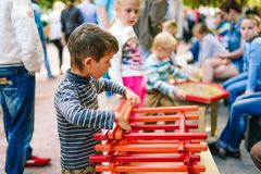 Rusland, stad Moskou - September 6, 2014: De jongen verzamelt de ontwerper van houten stokken Het scherpe kind verzamelt houten stock afbeeldingen