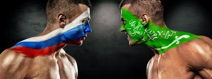 Rusland versus Saudi-Arabië Twee voetbal of voetbalventilators met vlaggen van aangezicht tot aangezicht Wereldbeker 2018 Stock Afbeelding