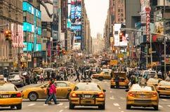 Rusningstid med taxiar och smältdegelfolk i New York Arkivfoton