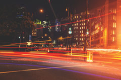 Rusningstidbiltrafikljus skuggar i London på natten royaltyfri foto