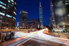 Rusningstidtrafik som rusar till och med en upptagen genomskärning nära Taipei 101 i huvudstaden av Taiwan Royaltyfri Foto