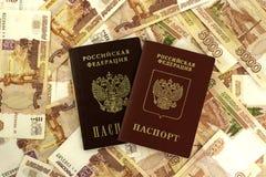 Ruso extranjero y pasaporte nacional en un fondo del dinero Foto de archivo