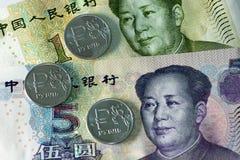 Ruso monedas de una rublo y billetes de banco del yuan Foto de archivo