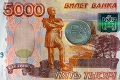 Ruso una moneda de la rublo y cinco mil rublos de billetes de banco Foto de archivo libre de regalías