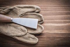 Ruspa spianatrice della pittura e del guanto sul bordo di legno Fotografie Stock Libere da Diritti