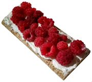 Ruspberries on a pieace of crispy bread with cream. stock photo