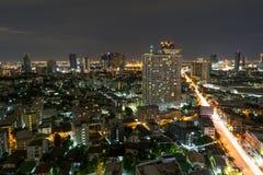Ruspe spianatrici della città di Bangkok con alta costruzione alla notte Fotografia Stock