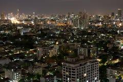 Ruspe spianatrici della città di Bangkok con alta costruzione alla notte Fotografia Stock Libera da Diritti
