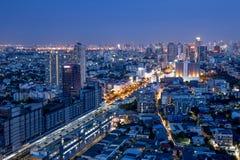 Ruspe spianatrici della città di Bangkok con alta costruzione alla notte Immagini Stock Libere da Diritti