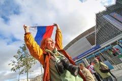 Russain有俄罗斯旗子的爱好者女孩在体育场竞技场附近 免版税库存图片