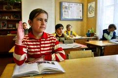 Russe, Dorfschule, Klassenzimmer, Schulmädchen hebt seine Hand an. Lizenzfreies Stockbild