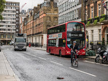 Russell Square buss och cyklist på den Augusti eftermiddagen Arkivfoto