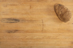 Russet Potato on Countertop. A russet potato sits on a worn butcher block counter stock photography
