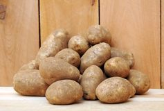Russet potatoes. A pile of russet potatoes on wooden shelf Stock Photo