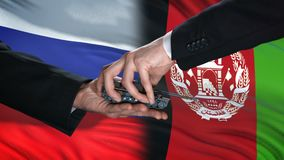 Russia and Afghanistan officials exchanging tank for money, flag background. Stock footage stock illustration