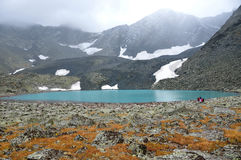 Russia, The Altai mountains, tourists walking near upper Acchan Akchan lake in overcast weather Stock Images