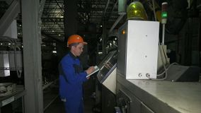 RUSSIA, ANGARSK - JUNE 8, 2018: Operator monitors control panel of production line. Manufacture of plastic water pipes. Of the factory. Process of making royalty free stock photography