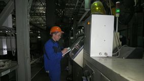 RUSSIA, ANGARSK - JUNE 8, 2018: Operator monitors control panel of production line. Manufacture of plastic water pipes. Of the factory. Process of making stock image
