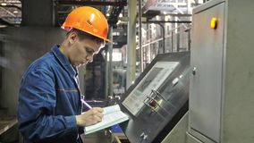 RUSSIA, ANGARSK - JUNE 8, 2018: Operator monitors control panel of production line. Manufacture of plastic water pipes. Of the factory. Process of making royalty free stock photos