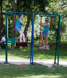 Russia, Arkhipo-Osipovka, June 20, 2016: adult girl riding on a swing in children`s park Royalty Free Stock Images