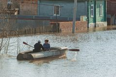 Russia, Balashov April 24, 2018. People in a boat sail along a flooded street to their house. Sunken under water fence street. Houses property. Flooded during stock photos