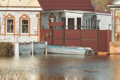 Russia, Balashov April 24, 2018. Private houses sunken underwater flooded during the spring flood flow stream river. Boat Stock Photo