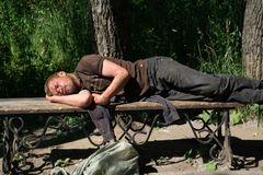 Russia Berezniki 15 July 2017 Homeless man in suit sleeping on bench at night with backpack royalty free stock image