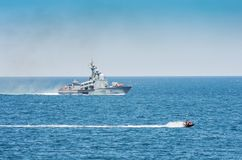 A warship and a hydrocycle in the sea royalty free stock photography
