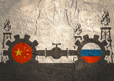 Russia and China flags on gears. Image relative to gas transit from Russia to China. Gears connected by gas pipe. National flags on cog wheels. Concrete textured Royalty Free Stock Photos