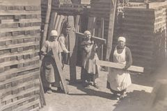 RUSSIA - CIRCA 1920s: Vintage photo of thee young women and man working in manufacture. RUSSIA - CIRCA 1920s: Vintage photo of thee young women and man working stock image