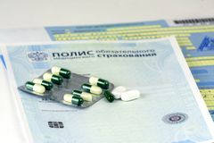Russia. Close-up, the Russian policy of Compulsory Health Insurance and sick leave with seals. The bottle of pills and a few pills stock photography