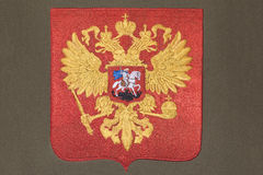 Russia coat of arms. Embroidery of Russia coat of arms on gray fabric stock images