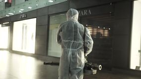 RUSSIA 06.04.2020. Covid-19 spreading. Workers in hazmat suits and respirator masks sprays disinfectant in office