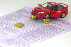 Russia, diagnostic card inspection machine, car insurance. The red car is on the columns of coins. Focus on the nearest coins. Clo. Russia, diagnostic card stock photo