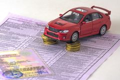 Russia, diagnostic card inspection machine, car insurance. Close up. The red car is on the columns of coins. Certificate of regist. Russia, diagnostic card stock photography