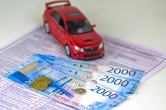 Russia, diagnostic card inspection machine, car insurance. The red car is on the form. Several Russian banknotes worth 2000 rubles. Focus on the nearest coins stock photo